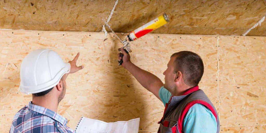 foreman wearing white hard hat applying caulk