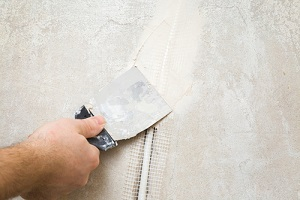 hands using spatula and plastering wall with putty