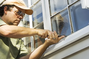 man removing old caulking from windows