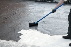 worker applying waterproofing material with roller for Commercial Waterproofing Services